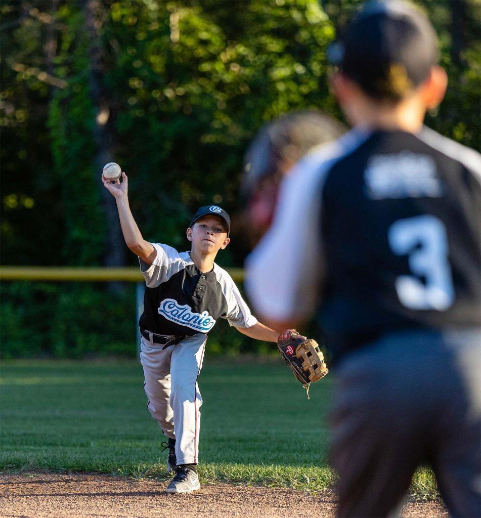 Fielder throwing baseball to baseman